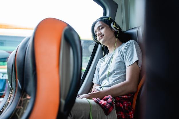 수면 헤드폰을 착용 한 젊은 남자가 버스 여행에서 창가에 앉아있는 동안 창에 기대어 있습니다.