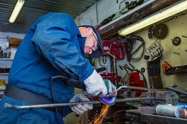 青いtシャツ、ゴーグル、建設用手袋を身に着けた若い男性の溶接工が金属製のアングルグラインダーをガレージで加工