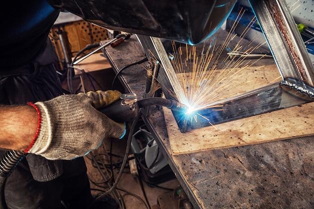 溶接マスクと建設用手袋をはめた若い男の溶接工が、金属溶接機を溶接する