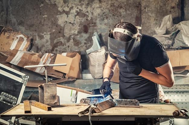 ワーク ショップでアーク溶接機で金属を溶接する若い男の溶接工
