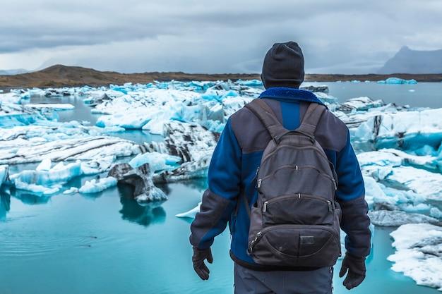 Молодой человек с рюкзаком смотрит на ледяное озеро йокулсарлон в золотом круге южной исландии