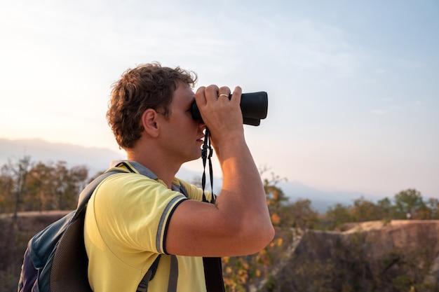 Молодой человек с рюкзаком за спиной наблюдает в бинокль с высоты гор