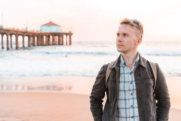 Молодой человек с рюкзаком гуляет по пляжу в лос-анджелесе с ярким закатом