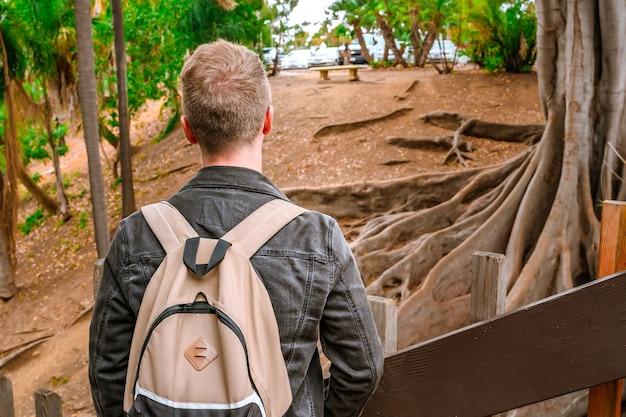 배낭을 메고 발보아 공원에 거대한 뿌리를 가진 나무가 있는 열대 우림을 걷는 청년