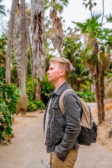 バックパックを持った若い男がバルボアパークの巨大な根を持つ木々のある熱帯雨林を歩きます