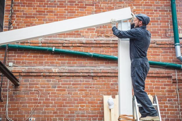 검은 색 건설 제복을 입은 수염 빌더가있는 젊은 남자, 회색 모자가 여름날 흰색으로 칠해진 나무 빔의 집을 짓습니다.