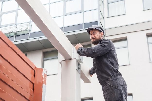 건설 검은 제복을 입은 수염 빌더가있는 청년, 회색 모자가 나무 빔의 집을 짓습니다.