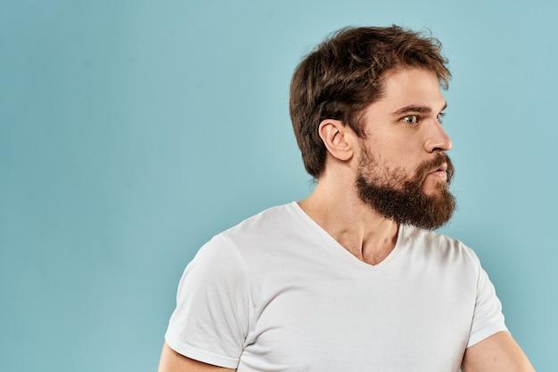 Молодой человек с бородой в футболке показывает разные эмоции, веселье, грусть, злость в студии на заднем плане.