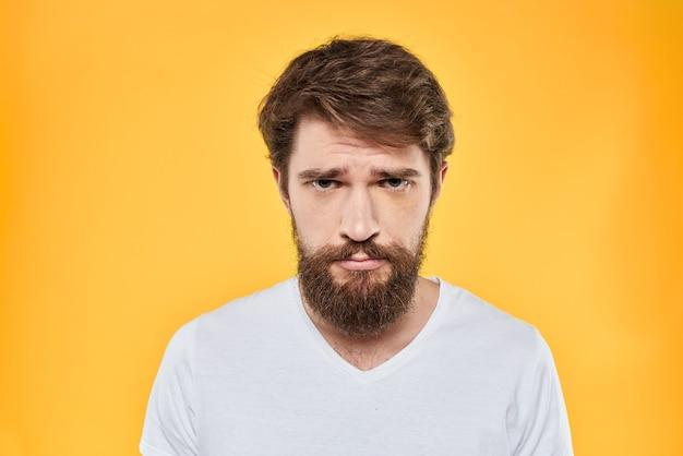 Tシャツにひげを持つ若い男は、背景にあるスタジオでさまざまな感情、楽しさ、悲しみ、怒りを示しています