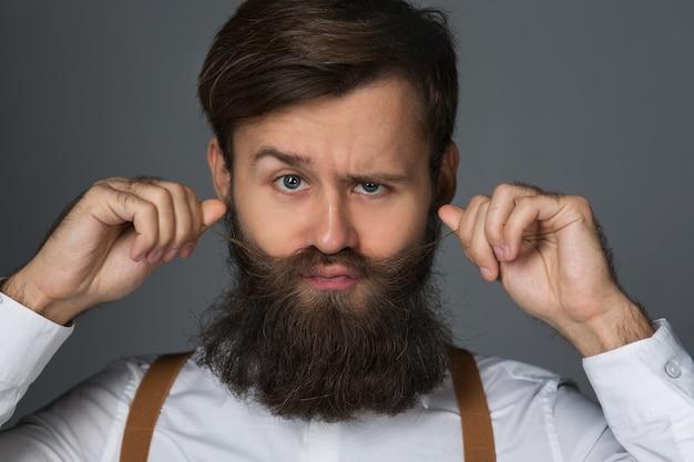 白いシャツと黄色のサスペンダーとズボンのひげを持つ若い男は、灰色の背景に彼のひげと口ひげに触れます