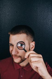 ひげを持つ若い男は虫眼鏡を通して見る。
