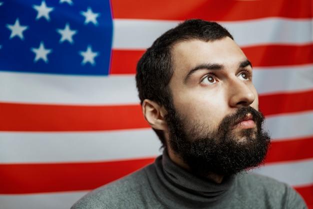 Молодой человек с бородой на фоне американского флага. крупный план. день независимости. бунты и гражданская война.