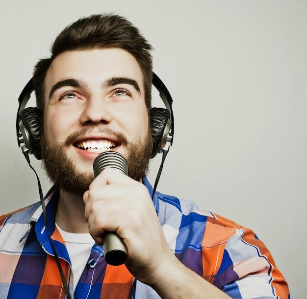 Молодой человек с бородой, одетый в рубашку, держит микрофон и поет, хипстерский стиль. на сером фоне.