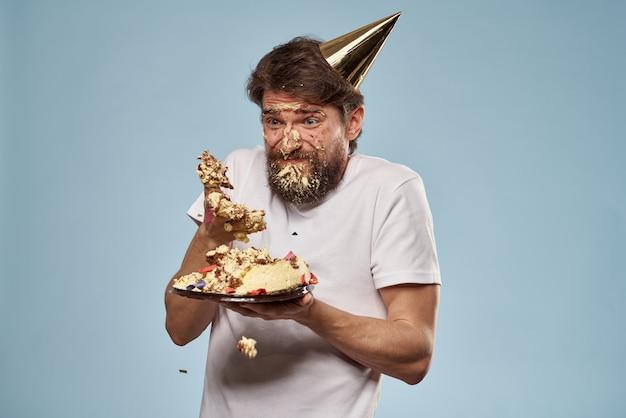 Молодой человек с праздничным тортом упал ему на лицо с тортом, его лицо в торте
