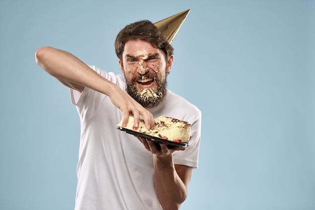 Молодой человек с праздничным тортом упал лицом с тортом, лицо в торте