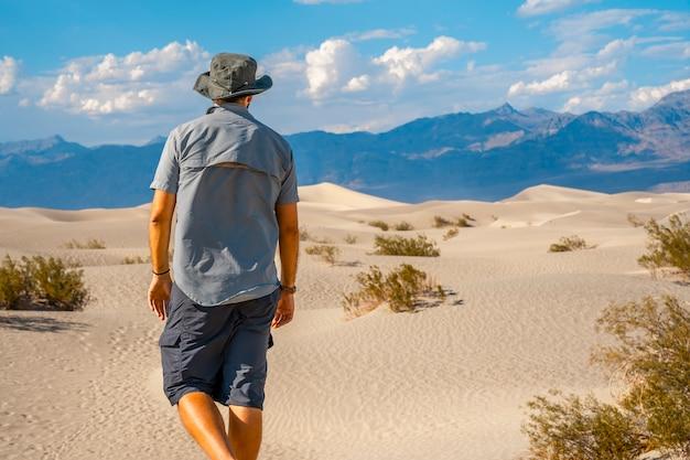 カリフォルニア州デスバレーの砂漠で青いシャツを着た若い男。アメリカ