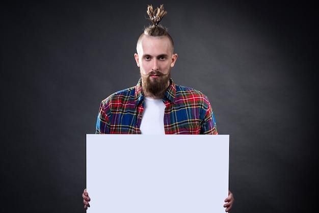 ふさふさしたあごひげとスタイリッシュなヘアカットを持つ若い男は、スタジオで空のレターヘッドを保持します