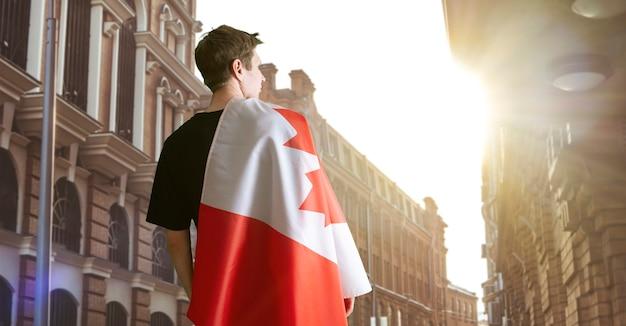 Soulders 애국심과 자랑스러운 감정에 캐나다 국기를 가진 청년