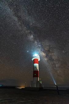 Молодой человек с фонариком у маяка фуэнкалиенте с млечным путем на маршруте вулканов к югу от острова ла пальма, канарские острова, испания