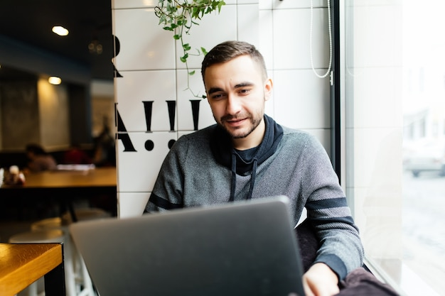 Молодой человек с ноутбуком в кафе. внештатный работник
