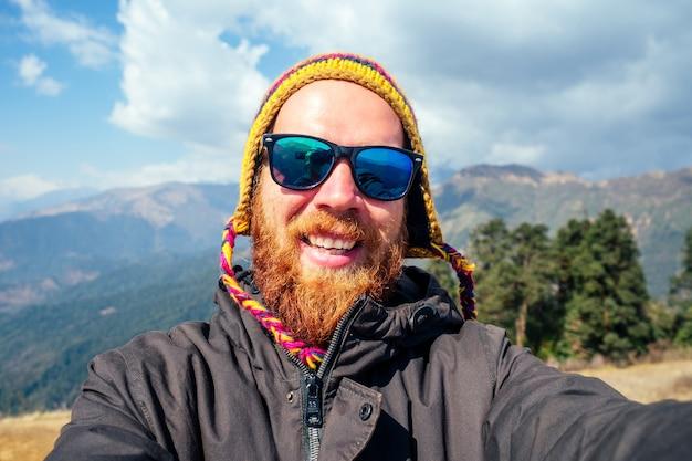山の中で赤いあごひげとバックパックを持った若い男が自分撮りをします。山でのアクティブなレクリエーションと観光の概念。春のネパール。