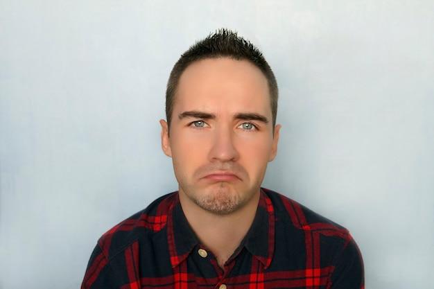 슬픈 표정의 청년. 좌절된 녀석. 슬픈 남자의 초상화입니다. 파란색 배경에 대해 젊은 현대 유행 남자의 초상화. 남자는 눈물로 운다.