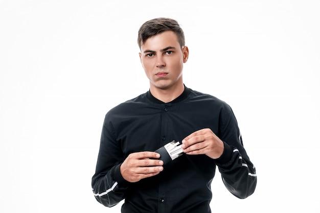 Молодой человек с серьезным лицом достает сигареты из черной пачки. плохие привычки. бросить курить. изолированный фон