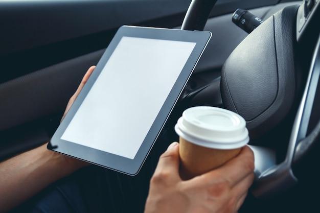 車のホイールで手にタブレットを持つ若い男