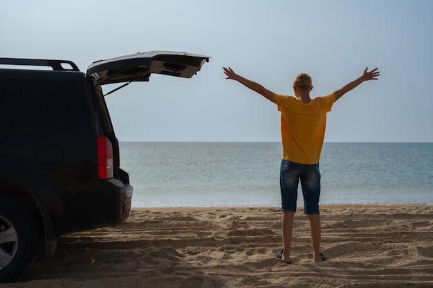 オフロード車を持った青年が旅をし、海沿いの砂浜の海岸に立つ