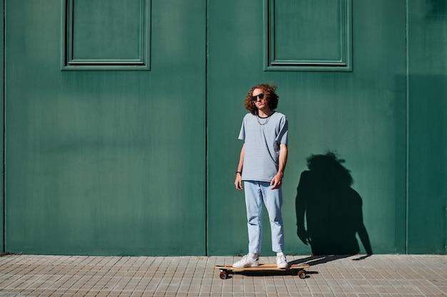 곱슬머리를 한 젊은 남자가 뒤에 녹색 벽을 가지고 야외에서 스케이트를 탔다