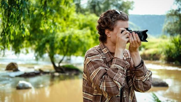 近くの自然、川、緑の中でカメラを使用して写真を撮る巻き毛の若い男