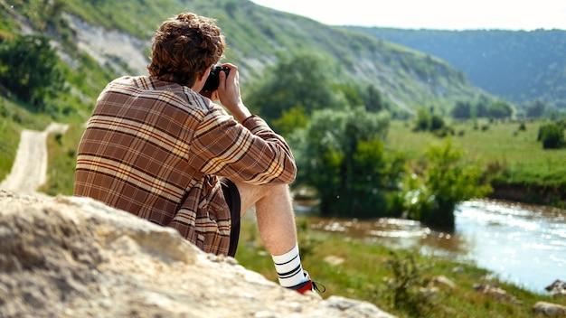 岩の上に座って自然の中でカメラを使用して写真を撮る巻き毛の若い男