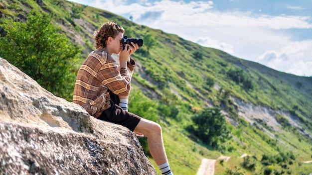岩だらけの丘の斜面に座って、自然の中でカメラを使用して写真を撮る巻き毛の若い男