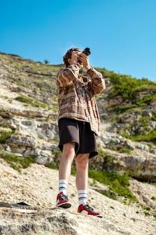 岩だらけの丘の斜面にとどまり、自然の中でカメラを使用して写真を撮る巻き毛の若い男