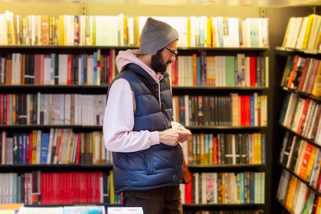Молодой человек в очках и шляпе в книжном магазине выбирает литературу.