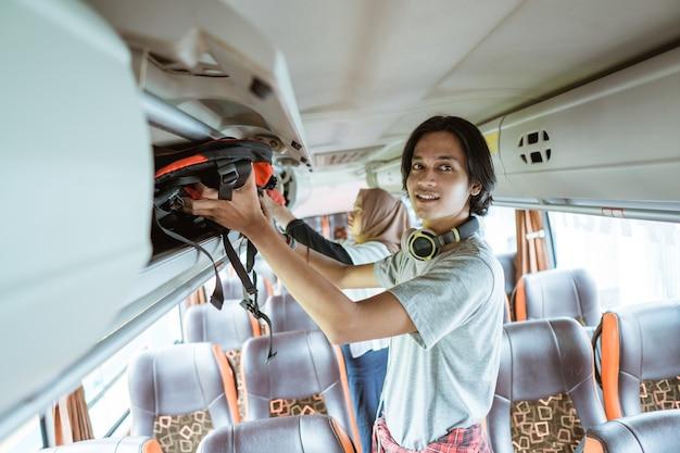 バスが出発する前にバスに立っている間、ヘッドフォンを持った若い男が棚にバッグを置きました