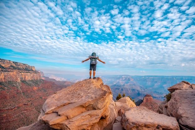 サウスカイバブトレイルヘッドの降下の視点で両手を広げた若い男。アリゾナ州グランドキャニオン