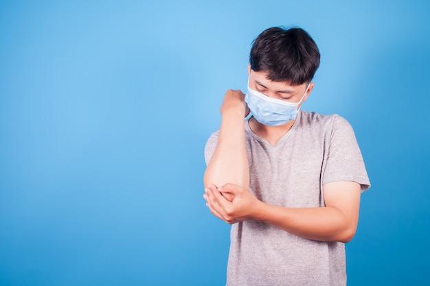 파란색 배경에 팔꿈치에 통증이 있는 젊은 남자. 건강 관리 및 문제 통증 완화 개념