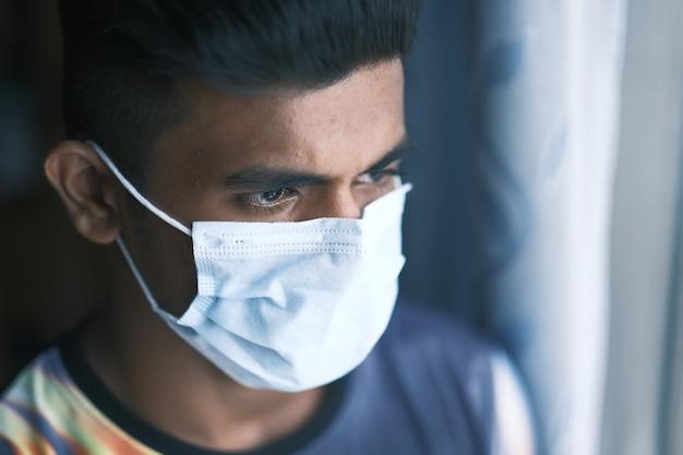 창을 통해보고 보호 마스크와 젊은 남자