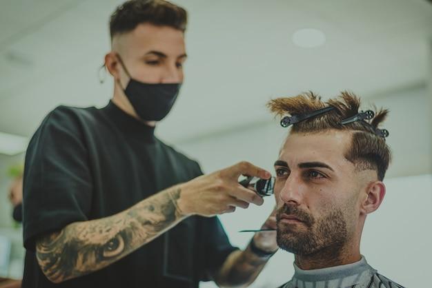 入れ墨の腕を持つ若い男は理髪店で男の髪をカットします