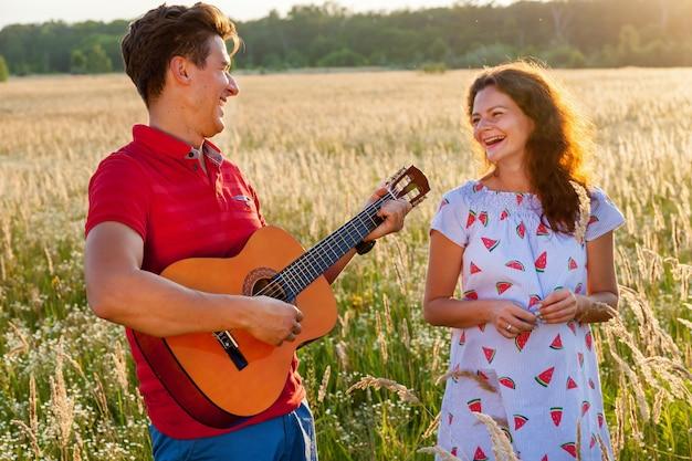 기타를 든 젊은 남자가 화창한 날 밀밭에서 임신한 아내 옆에 서 있습니다. 자연 속에서 임신한 가족 사진 촬영