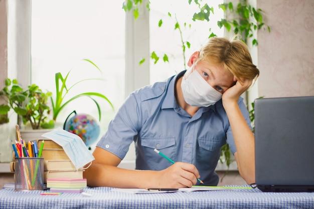 青いシャツとマスクを着た白い髪の若い男が机に座って書いている。教育の概念。エピデミック。