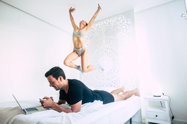 Молодой человек работает с ноутбуком и мобильным телефоном на плохом, ложится в режиме релаксации, а девушка прыгает и играет как сумасшедшая.