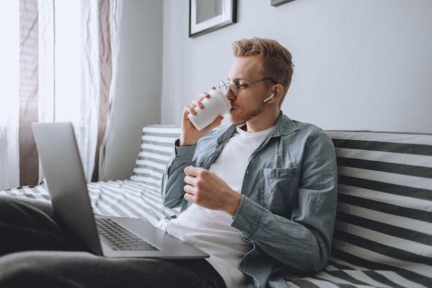 Молодой человек работает дома с ноутбуком и пьет кофе