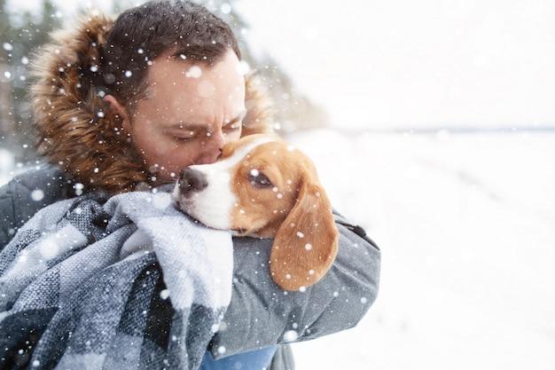 한 젊은 남자가 그의 가장 친한 친구 비글 개를 따뜻한 담요에 싸서 그를 따뜻하게합니다.