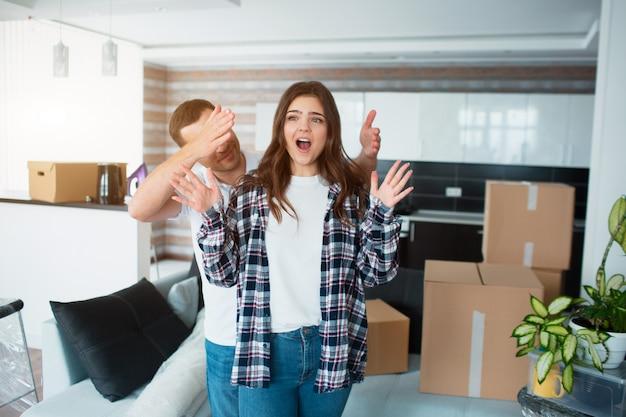 家のリビングルームにいる若い夫婦が、開梱された箱の近くに立っています。ねえ、新しい家に満足しています。引っ越し、家を買う、アパートのコンセプト。