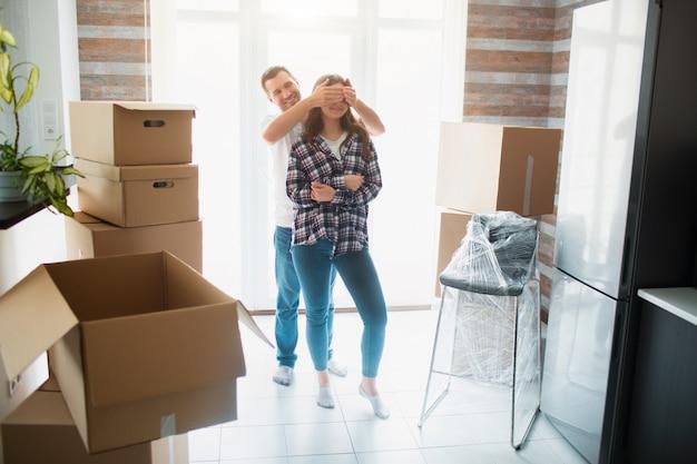 家のリビングルームにいる若い夫婦が、開梱された箱の近くに立っています。彼らは新しい家に満足しています。引っ越し、家を買う、アパートのコンセプト。