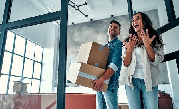 Молодая семейная пара в гостиной распаковывает коробки с вещами. счастливые муж и жена веселятся, с нетерпением ждут нового дома. переезд, покупка дома, концепция квартиры.