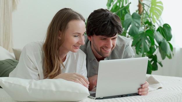 Молодая семейная пара лежит дома на кровати, пользуется ноутбуком и обсуждает насущные вопросы.
