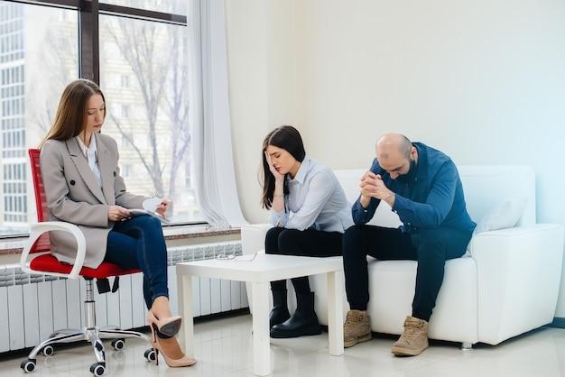 男性と女性の若い夫婦がセラピーセッションで心理学者と話します。心理学。